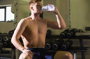 Muscular handsome man sitting on bench drinking from water bottleの写真素材 [FYI02234217]