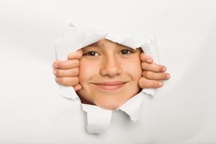 Cute little girl peeking through paperの写真素材 [FYI02234257]