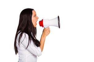Young woman shouting through megaphoneの写真素材 [FYI02234277]