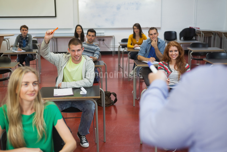Student raising his hand to ask a question in classの写真素材 [FYI02234288]