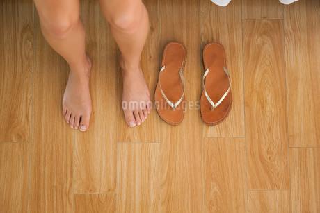 Woman sitting on edge of bed beside her flip flopsの写真素材 [FYI02234295]