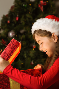 Little girl opening a magical christmas giftの写真素材 [FYI02234297]