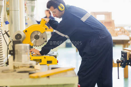 Craftsman with safety glasses sawing woodの写真素材 [FYI02234299]