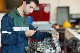 Calm repairman repairing an engineの写真素材 [FYI02234331]