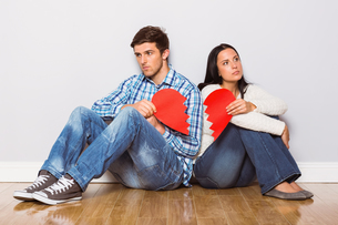 Young couple sitting on floor with broken heartの写真素材 [FYI02234393]