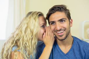 Blonde young woman whispering something to her boyfriendの写真素材 [FYI02234517]