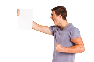 Angry man shouting at piece of paperの写真素材 [FYI02234533]