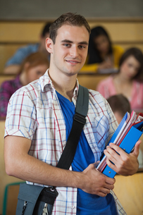 Cheerful handsome student standing in front of his class in lecture hallの写真素材 [FYI02234536]