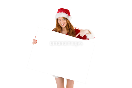 Festive redhead smiling at camera holding posterの写真素材 [FYI02234560]