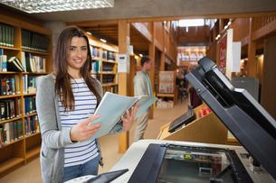 Smiling brunette student standing next to photocopierの写真素材 [FYI02234562]