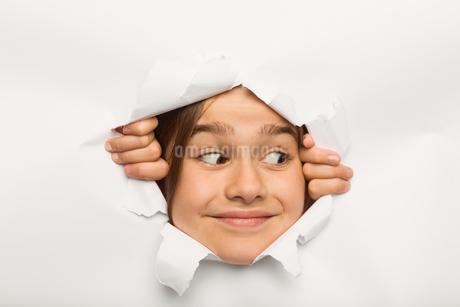 Cute little girl peeking through paperの写真素材 [FYI02234565]