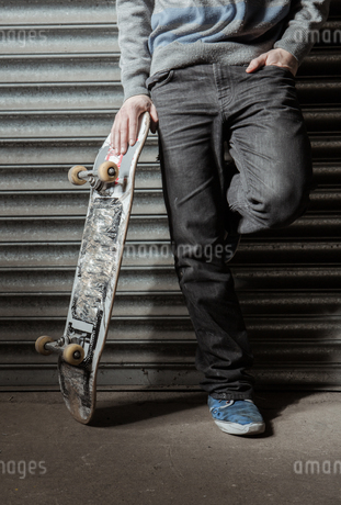 Skater standing against metal shuttersの写真素材 [FYI02234592]