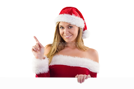 Festive blonde smiling and pointingの写真素材 [FYI02234612]