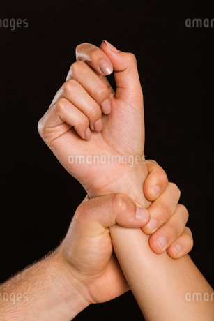 Male hand grabbing female wristの写真素材 [FYI02234697]