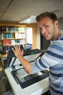 Smiling handsome student using photocopierの写真素材 [FYI02234712]