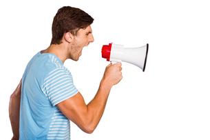 Young man shouting through megaphoneの写真素材 [FYI02234763]