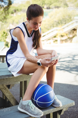 Smiling woman using smart phone while sitting on picnic tableの写真素材 [FYI02234817]