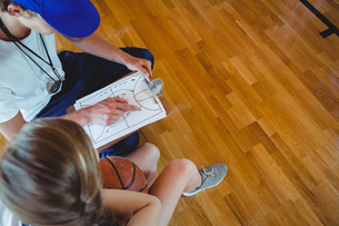 Male coach explaining diagram to female basketball playerの写真素材 [FYI02234840]