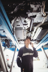 Female mechanic talking on mobile phone under a carの写真素材 [FYI02234859]