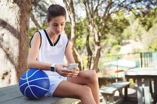 Female basketball player using mobile phoneの写真素材 [FYI02234867]