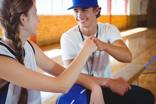 Smiling coach doing fist bump with female basketball playerの写真素材 [FYI02234881]
