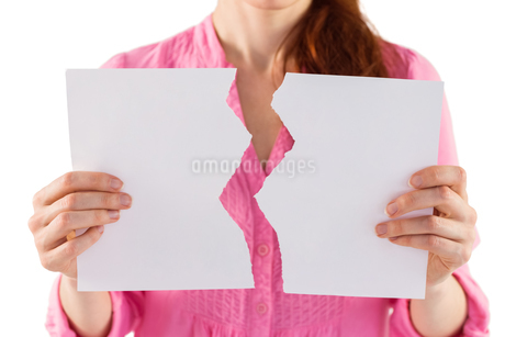 Woman holding torn sheet of paperの写真素材 [FYI02234890]
