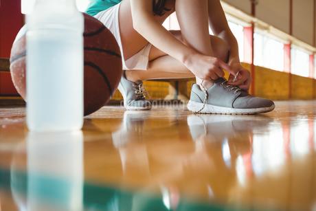 Woman tying shoelace while crouching on floorの写真素材 [FYI02234934]