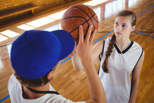 High angle view of male coach training female basketball playerの写真素材 [FYI02234960]