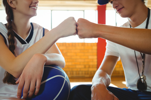 Close-up of female basketball player doing fist bump with male coachの写真素材 [FYI02234995]