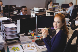 Portrait of businesswoman having snack while colleagues working in creative officeの写真素材 [FYI02235015]