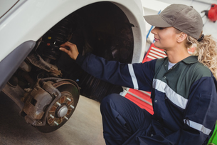 Female mechanic examining a car wheel disc brakeの写真素材 [FYI02235032]