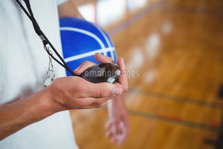 Midsection of basketball coach with stopwatchの写真素材 [FYI02235046]