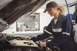 Female mechanic servicing carの写真素材 [FYI02235059]