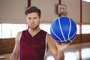 Portrait of serious basketball player holding ballの写真素材 [FYI02235070]