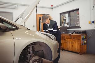 Female mechanic servicing carの写真素材 [FYI02235106]