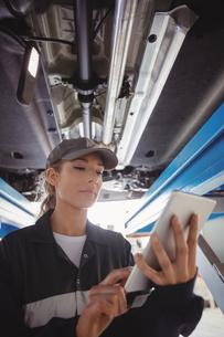 Female mechanic using digital tablet under a carの写真素材 [FYI02235108]