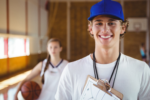 Portrait of smiling male coach with basketball playerの写真素材 [FYI02235220]