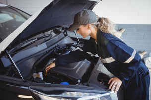 Female mechanic servicing carの写真素材 [FYI02235226]