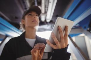 Female mechanic using digital tablet under a carの写真素材 [FYI02235254]