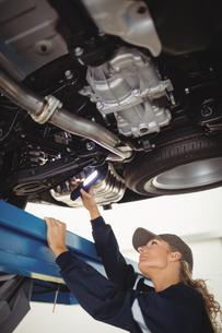 Female mechanic examining a car with flashlightの写真素材 [FYI02235293]