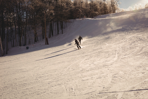 Two skiers skiing in snowy alpsの写真素材 [FYI02235300]