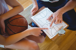 Close up of coach explaining diagram to female basketball playerの写真素材 [FYI02235354]