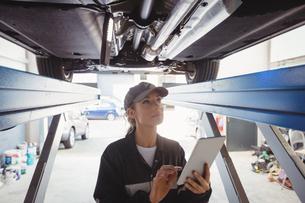 Female mechanic using digital tablet under a carの写真素材 [FYI02235475]