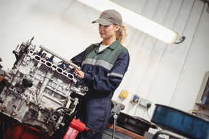 Female mechanic checking a car partsの写真素材 [FYI02235503]