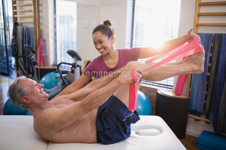 Smiling female therapist looking at male patient pulling resistance band while lying on bedの写真素材 [FYI02235576]