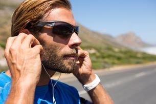 Athlete listening music from headphones against skyの写真素材 [FYI02235586]
