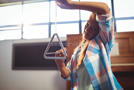 Portrait of girl playing triangle in classroomの写真素材 [FYI02235609]