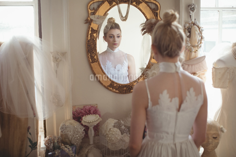Young bride in a white dress looking into mirrorの写真素材 [FYI02235611]
