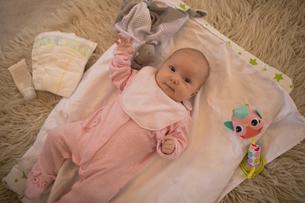 Cute baby lying on carpet in living roomの写真素材 [FYI02235619]