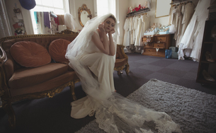 Thoughtful young bride in a white dress sitting on sofaの写真素材 [FYI02235623]